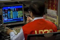 Un operador trabajando en la bolsa de Hong Kong, jul 8, 2015.Las bolsas de Asia subían levemente y el dólar se debilitaba el lunes junto a los precios del petróleo, en medio del temor a que los países productores de crudo no logren acordar un recorte al bombeo en su reunión de esta semana. REUTERS/Tyrone Siu