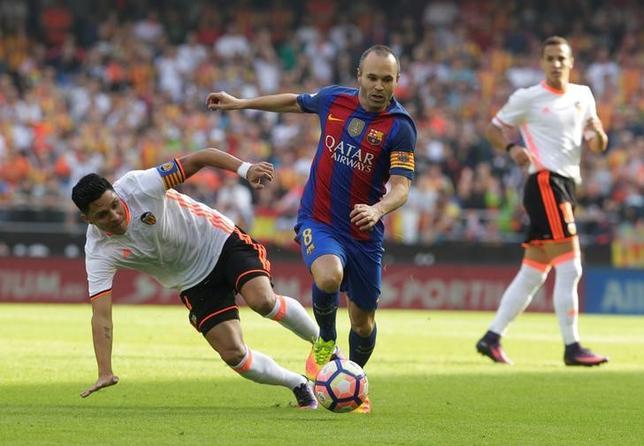 11月28日、サッカーのスペイン1部、バルセロナのスペイン代表MFアンドレス・イニエスタ(中央)は、12月3日にホームで行うレアル・マドリードとの今季初の伝統の一戦、「クラシコ」で戦列復帰する見通しとなった。バレンシアで10月撮影(2016年 ロイター/Heino Kalis)