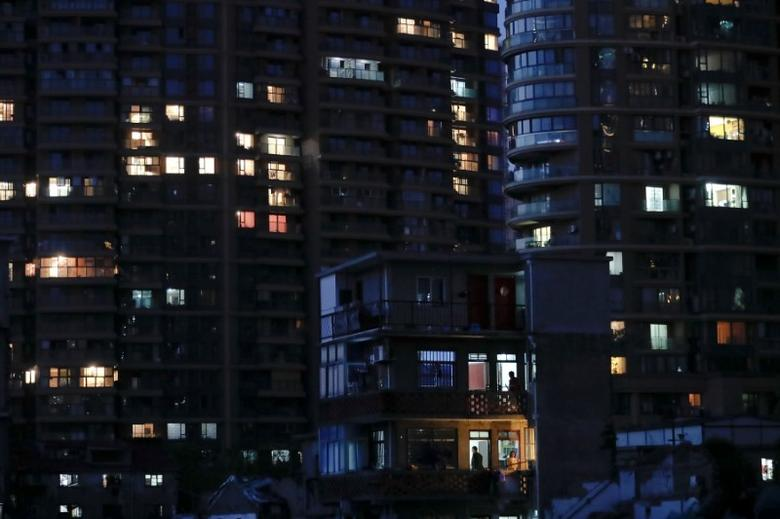 An old house is seen in front of new apartment buildings in Guangfuli neighbourhood, in Shanghai, China, April 18, 2016. REUTERS/Aly Song