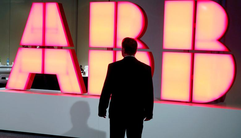 A man stands in front of the logo of Swiss engineering group ABB before a news conference in Zurich, Switzerland October 4, 2016. REUTERS/Arnd Wiegmann/File Photo