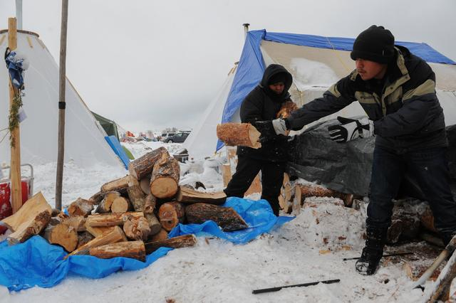 People prepare wood for a fire in the Oceti Sakowin camp during a protest against plans to pass the Dakota Access pipeline near the Standing Rock Indian Reservation, near Cannon Ball, North Dakota, U.S. November 30, 2016. REUTERS/Stephanie Keith
