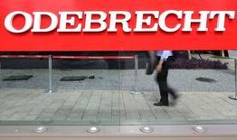 Homem caminha atrás de placa da Odebrecht na sede da empresa em São Paulo 22/03/2016 REUTERS/Paulo Whitaker