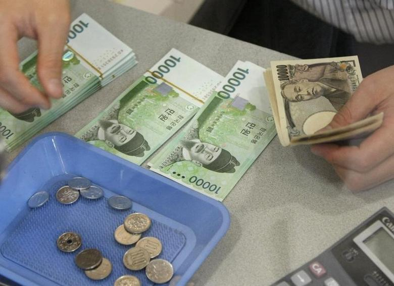 A Currency Dealer Counts Anese Yen And Korean Won At Money Exchange Bureau In