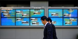 Hombres caminan frente a unas pantallas que muestra el índice Nikkei y otras divisas afuera de una correduría en Tokio, Japón. 6 de julio de 2016.El índice Nikkei de la bolsa de Tokio cayó el viernes, luego de que los inversores recogieron ganancias antes del reporte de unos datos de empleo en Estados Unidos más tarde en el día, pero el referencial logró anotar su cuarta ganancia semanal consecutiva.   REUTERS/Toru Hanai