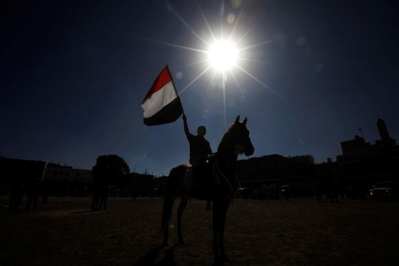 A Houthi rebel holds up the Yemen flag as he rides a horse during a rally held to mobilize fighters for fighting against government forces, in Sanaa, Yemen, December 1, 2016. REUTERS / Mohammed Sayaghi