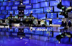 People pass a television installation at the Panasonic pavilion before the start of the IFA consumer electronics fair in Berlin, August 29, 2012.  REUTERS/Tobias Schwarz/File Photo