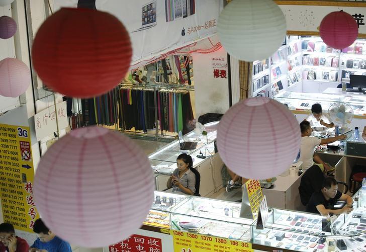 Sales people wait for customers at booths selling mobile phones in Beijing September 3, 2013.  REUTERS/Kim Kyung-Hoon/Files