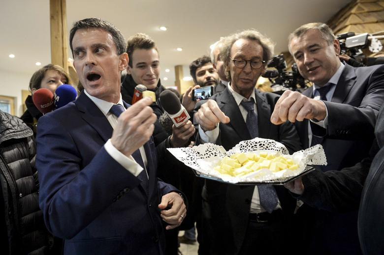 French politician Manuel Valls (L), candidate for January's Socialist presidential primary, holds a piece of cheese as he visits the Fruitieres de Lomont cheese company, in Noirefontaine, France, December 7, 2016.    REUTERS/Sebastien Bozon/Pool