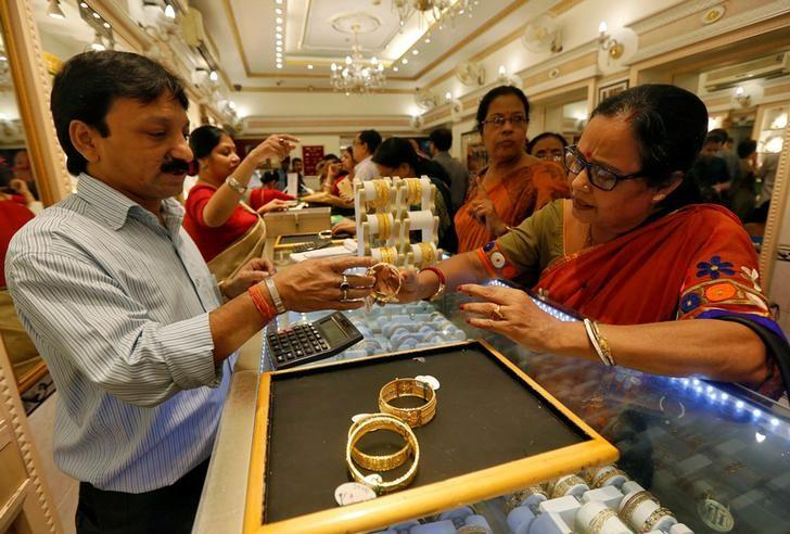 A salesman shows gold bangles to a customer at a jewellery showroom during Dhanteras, a Hindu festival associated with Lakshmi, the goddess of wealth, in Kolkata, India October 28, 2016. REUTERS/Rupak De Chowdhuri
