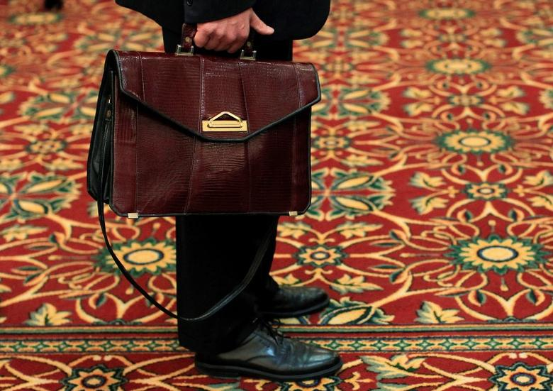 A man holds his briefcase while waiting in line during a job fair in Melville, New York July 19, 2012.  REUTERS/Shannon Stapleton/Files