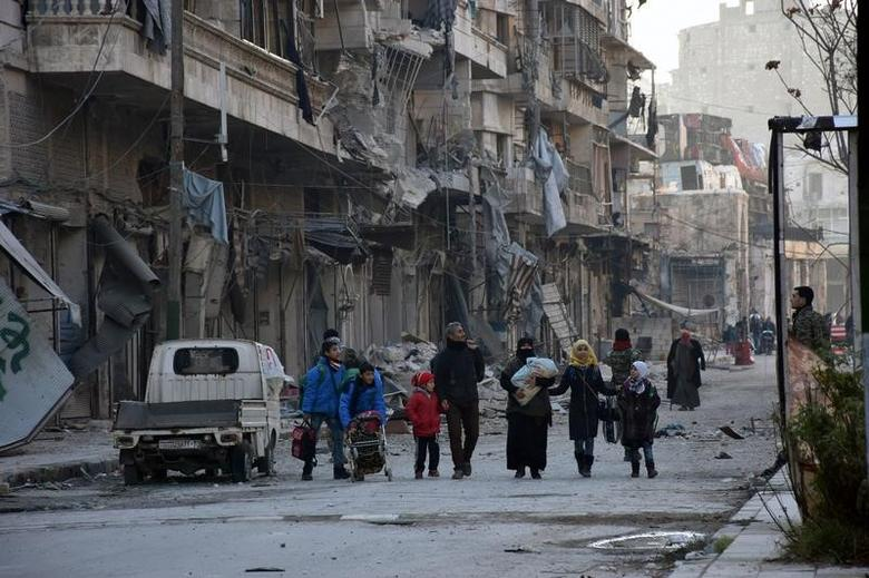People, who evacuated the eastern districts of Aleppo, carry their belongings as they arrive in a government held area of Aleppo, Syria, in this handout picture provided by SANA on December 7, 2016. SANA/Handout via REUTERS