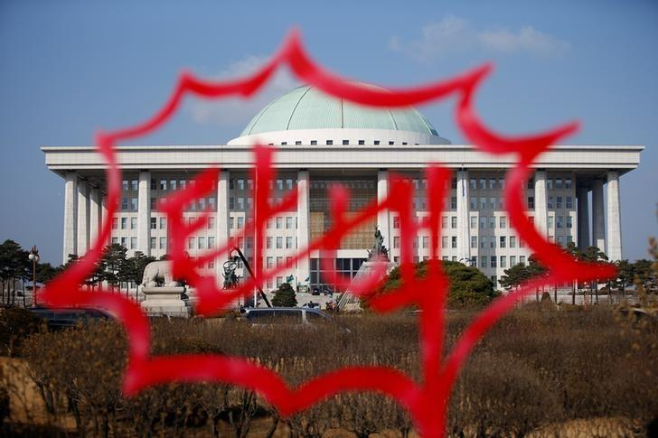 The National Assembly is seen through a sculpture installed by protesters bearing a message that reads ''Impeachment'' ahead of impeachment vote in Seoul, South Korea, December 9, 2016.  REUTERS/Kim Hong-Ji