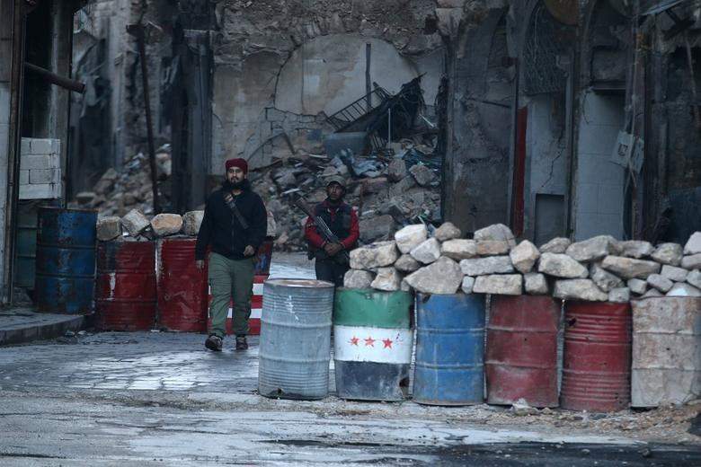 A rebel fighter stands with his weapon near damaged buildings, and barricades with a Free Syrian Army flag drawn(C), in rebel-held besieged old Aleppo, Syria December 2, 2016. REUTERS/Abdalrhman Ismail