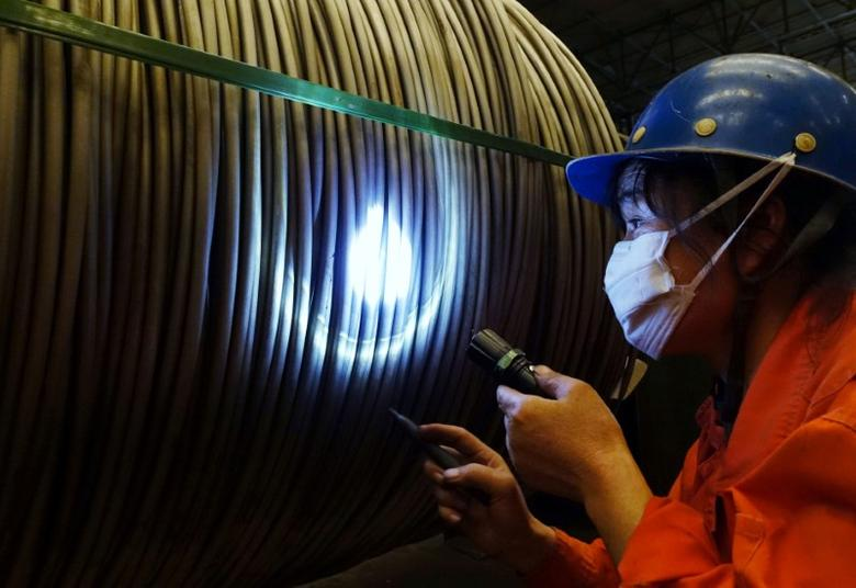 A worker verifies a product at a steel factory in Dalian, Liaoning province, China September 1, 2016. China Daily/via REUTERS