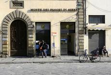 Люди пользуются банкоматом в отделении Monte Dei Paschi во Флоренции 1 марта 2016 года. Италия готова влить средства в Monte dei Paschi di Siena, если проблемный банк не сможет получить необходимый капитал от инвесторов, сообщил источник в казначействе страны в понедельник. REUTERS/Tony Gentile/File photo