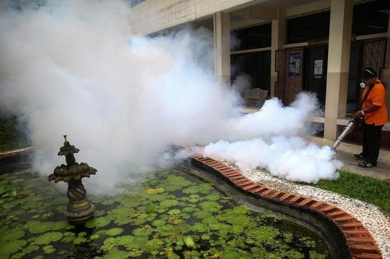 A city worker fumigates the area to control the spread of mosquitoes at a university in Bangkok, Thailand, September 13, 2016. REUTERS/Athit Perawongmetha