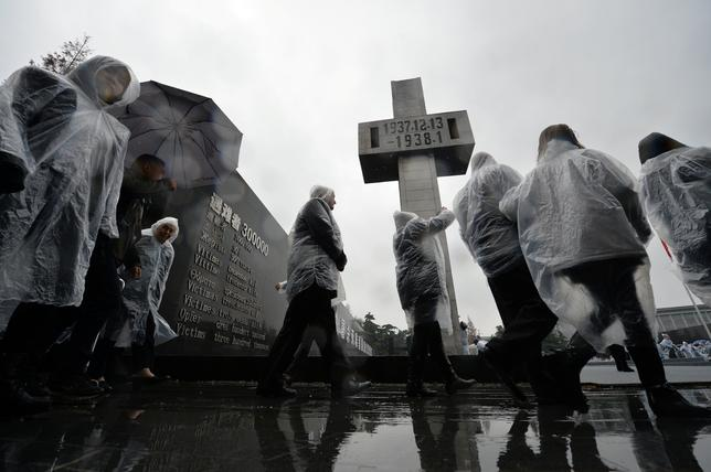 People walk past a monument as China holds a memorial ceremony to mark the National Memorial Day for Nanjing Massacre Victims in Nanjing, Jiangsu province, China, December 13, 2016. REUTERS/Stringer