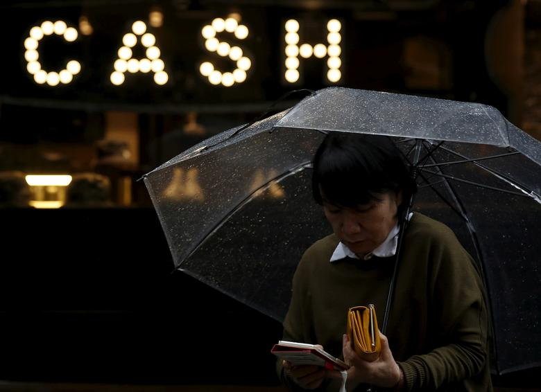 A pedestrian holding an umbrella and her wallet walks past the word ''CASH'', part of a sign on a street at a shopping district in Tokyo, Japan, March 7, 2016.  REUTERS/Yuya Shino/File Photo