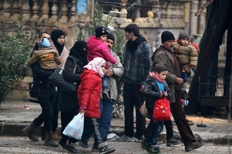 People carry their belongings as they flee deeper into the remaining rebel-held areas of Aleppo, Syria December 13, 2016. REUTERS/Abdalrhman Ismail