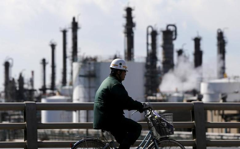 A worker cycles near a factory at the Keihin industrial zone in Kawasaki, Japan February 17, 2016.  REUTERS/Toru Hanai/File