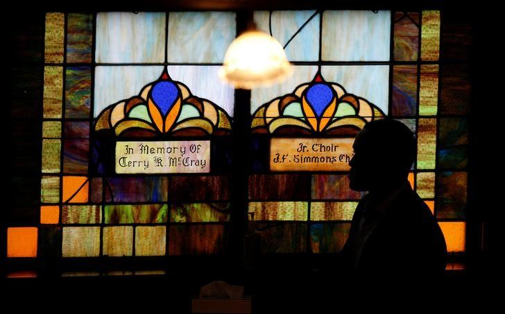 A person walks past a stain glass window at Emanuel AME Church before the start of a memorial ceremony marking the first anniversary of the shootings at the church, where nine people were killed by a gunman, in Charleston, South Carolina, U.S. June 17, 2016. REUTERS/Randall Hill