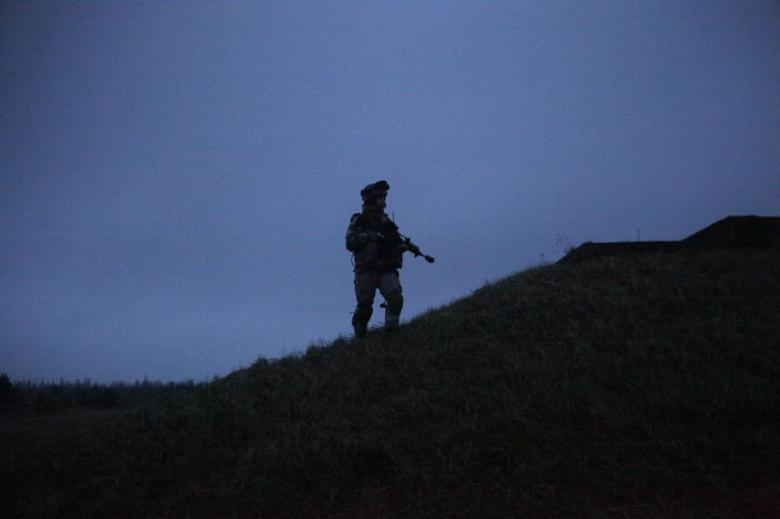 A Latvian army soldier patrols during the multinational military exercise ''Sabre Strike 2011'' in Adazi October 26, 2010. REUTERS/Ints Kalnins/File Photo