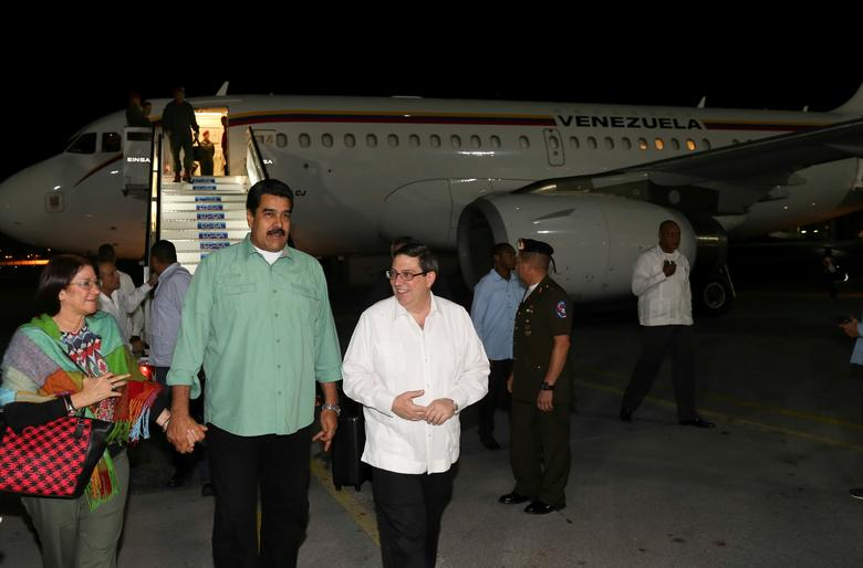 Venezuela's President Nicolas Maduro (2nd L) and his wife Cilia Flores (L) walk next to Cuban Foreign Minister Bruno Rodriguez (C), as they arrive at Havana's international Airport in Havana, Cuba December 14, 2016. Miraflores Palace/Handout via REUTERS