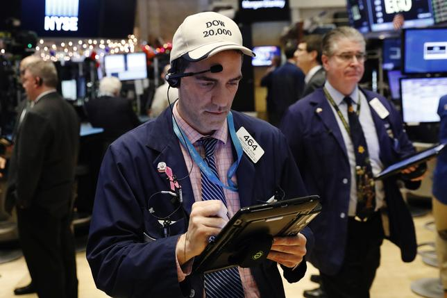 A trader wears a hat referencing the proximity of Dow Jones Industrial Average to 20,000 as he works on floor of the New York Stock Exchange (NYSE) shortly before the close of trading in New York, U.S., December 13, 2016.  REUTERS/Lucas Jackson