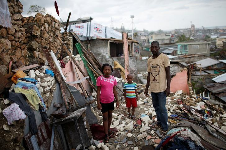 Prenille Nord, 42, poses for a photograph with his children Darline and Kervins among the debris of their destroyed house after Hurricane Matthew hit Jeremie, Haiti, October 17, 2016. REUTERS/Carlos Garcia Rawlins/Files