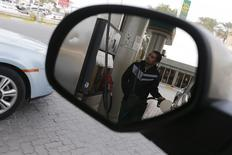 A fuel pump assistant fills cars with petrol at Budaiya Fueling Station west of Manama, Bahrain January 26, 2016. REUTERS/Hamad I Mohammed/File photo
