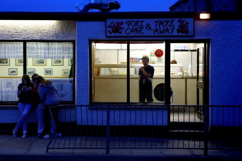 Youths sit outside a fish and chip shop in the town of Lerwick on the Shetland Islands April 3, 2014.  REUTERS/Cathal McNaughton/File Photo