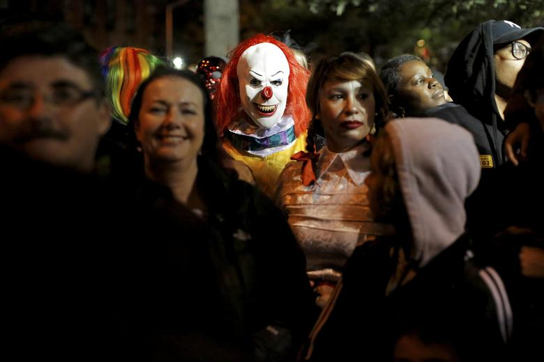 A person dressed in a clown costume stands amongst attendees during the Greenwich Village Halloween Parade in Manhattan, New York, U.S., October 31, 2016.  REUTERS/Andrew Kelly/File Photo