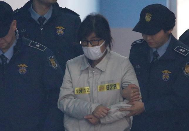 Choi Soon-sil (wearing white mask), a long-time friend of South Korean President Park Geun-hye who is at the center of the South Korean political scandal involving Park, arrives for her first court hearing  in Seoul, South Korea, December 19, 2016. REUTERS/Kim Hong-Ji
