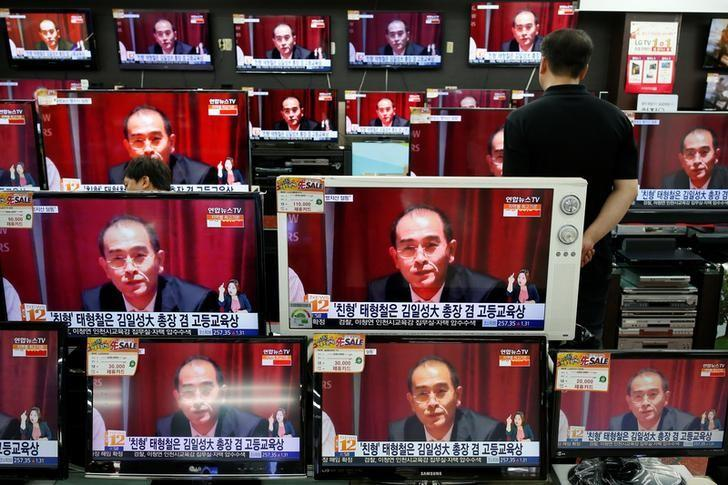 A sales assistant watches TV sets broadcasting a news report on Thae Yong Ho, North Korea's deputy ambassador in London, who has defected with his family to South Korea, in Seoul, South Korea, August 18, 2016.  REUTERS/Kim Hong-Ji