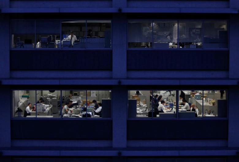 Office workers are pictured through building windows during dusk in Tokyo, Japan March 3, 2015. REUTERS/Issei Kato/File Photo