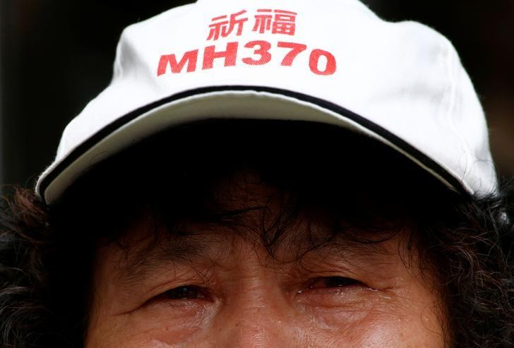 A family member of a passenger aboard Malaysia Airlines flight MH370 which went missing in 2014 reacts during a protest outside the Chinese foreign ministry in Beijing, July 29, 2016. The hat reads ''Pray for MH370'' REUTERS/Thomas Peter/Files