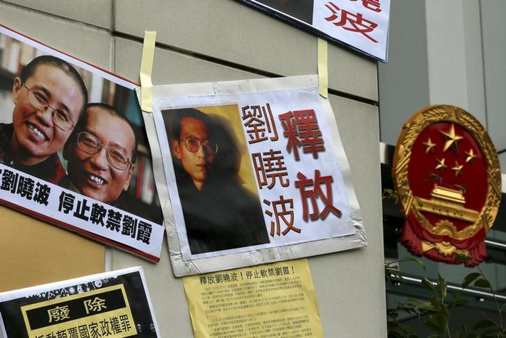 Signs and portraits of jailed Chinese Nobel Peace Prize laureate Liu Xiaobo and his wife Liu Xia are seen in front of the national emblem of China during a protest outside the Chinese liaison office in Hong Kong, China December 25, 2015. REUTERS/Tyrone Siu/Files