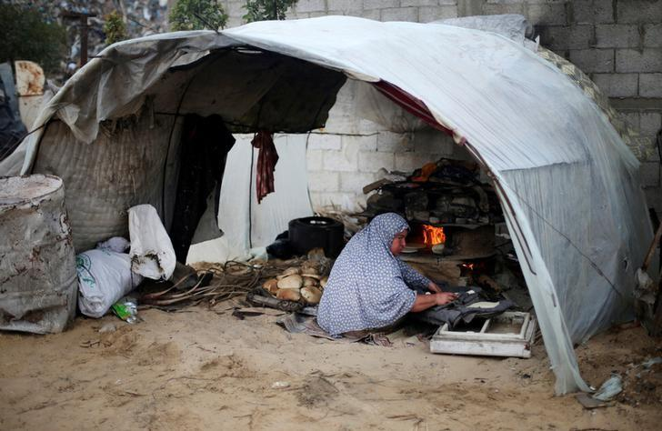 A Palestinian woman bakes bread in a tent outside her dwelling in Khan Younis in the southern Gaza Strip December 19, 2016. REUTERS/Ibraheem Abu Mustafa