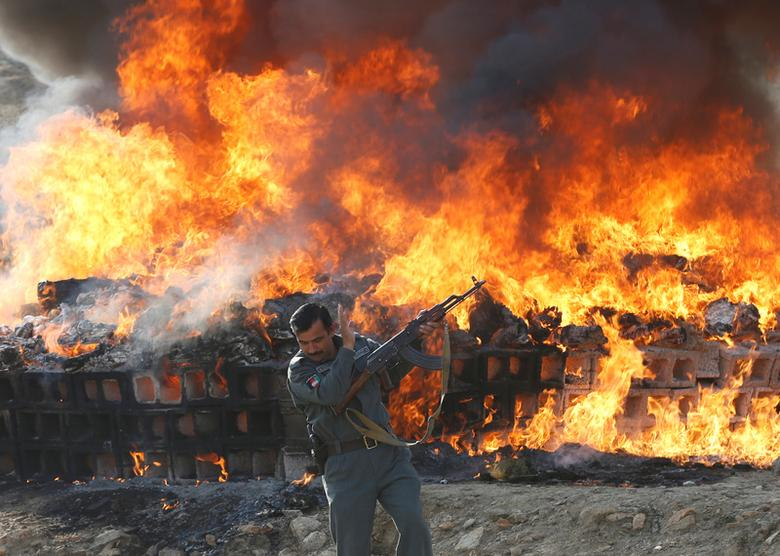 An Afghan officer shields his face in front of a burning pile of seized narcotics and alcoholic drinks, in the outskirts of Kabul, Afghanistan December 20, 2016. REUTERS/Omar Sobhani