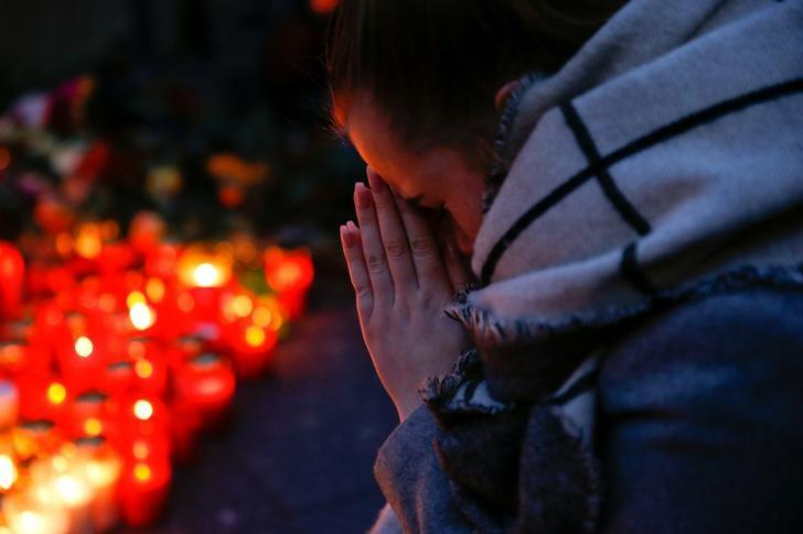 A woman prays next to lit candles at the Christmas market in Berlin, Germany, December 20, 2016, where a truck ploughed into the crowd on Monday.        REUTERS/Fabrizio Bensch