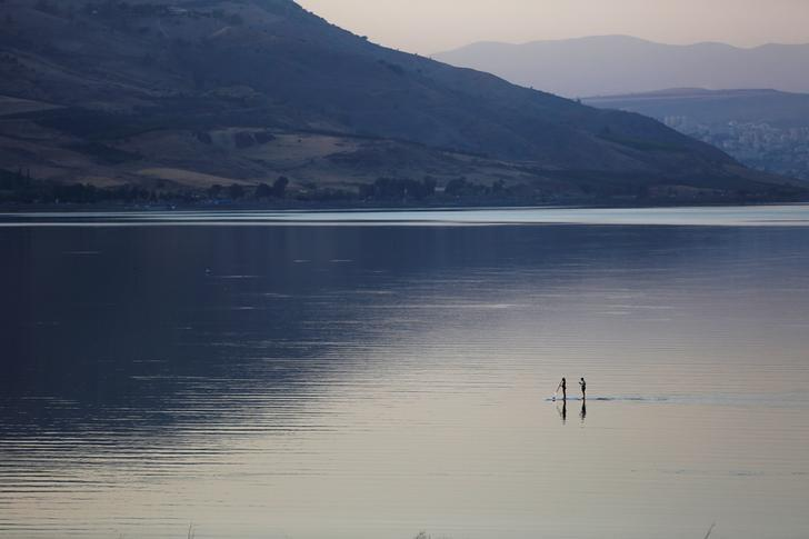 People paddle on a stand-up paddle board in the Sea of Galilee, northern Israel November 8, 2016. REUTERS/Ronen Zvulun