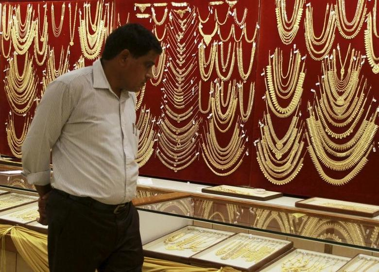 A customer looks at gold ornaments on display inside a jewelry showroom on the occasion of Akshaya Tritiya, a major gold buying festival, in the southern Indian city of Kochi April 21, 2015.  REUTERS/Sivaram V