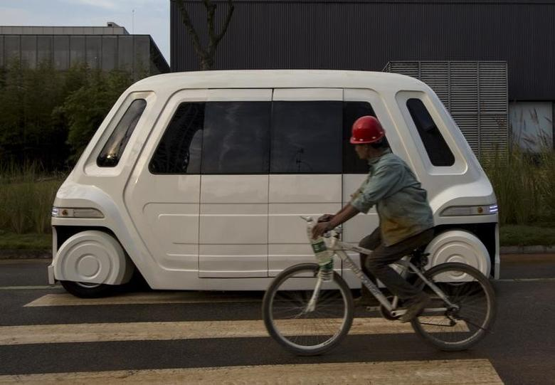 A worker rides a bike past a driverless vehicle at Vanke's Building Research Centre testing area in Dongguan, south China's Guangdong province November 2, 2015. REUTERS/Tyrone Siu