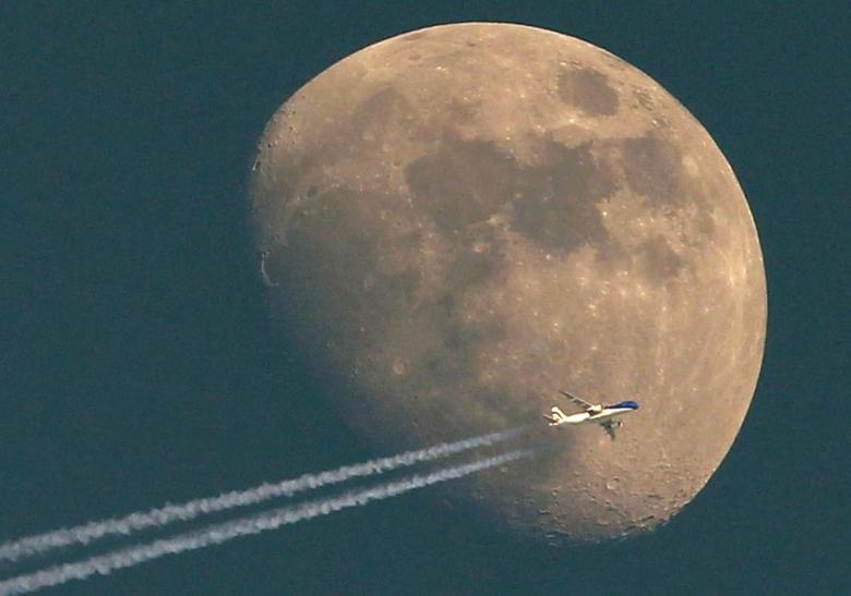 A jet, it's vapour trail streaming out behind, flies past the waxing moon over the city of Aarau April 24, 2010. REUTERS/Arnd Wiegmann