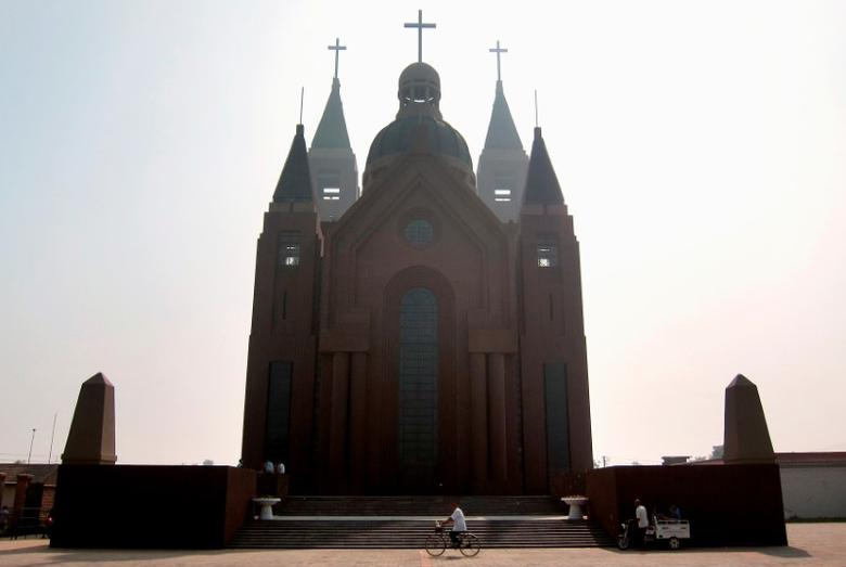 A man rides his bicycle past the steps of a large Catholic church in the village of Bai Gu Tun, located on the outskirts of the city of Tianjin, around 70 km (43 miles) south-east of Beijing July 17, 2012.  REUTERS/David Gray/File Photo