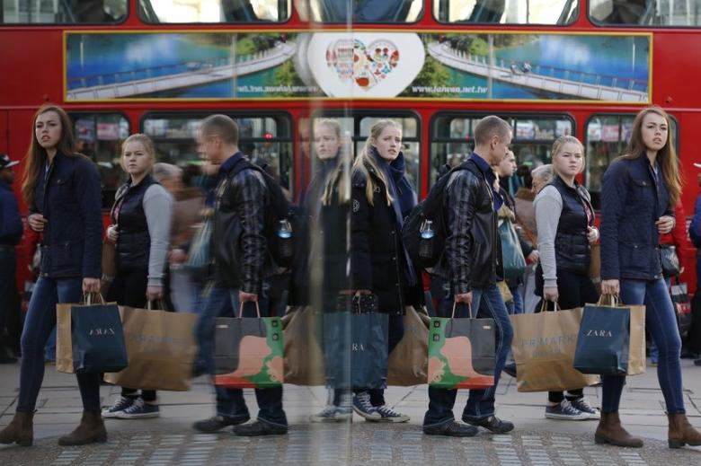 Shoppers are reflected in a window as they carry bags along Oxford street during the final weekend of shopping before Christmas in London December 20, 2014.  REUTERS/Luke MacGregor