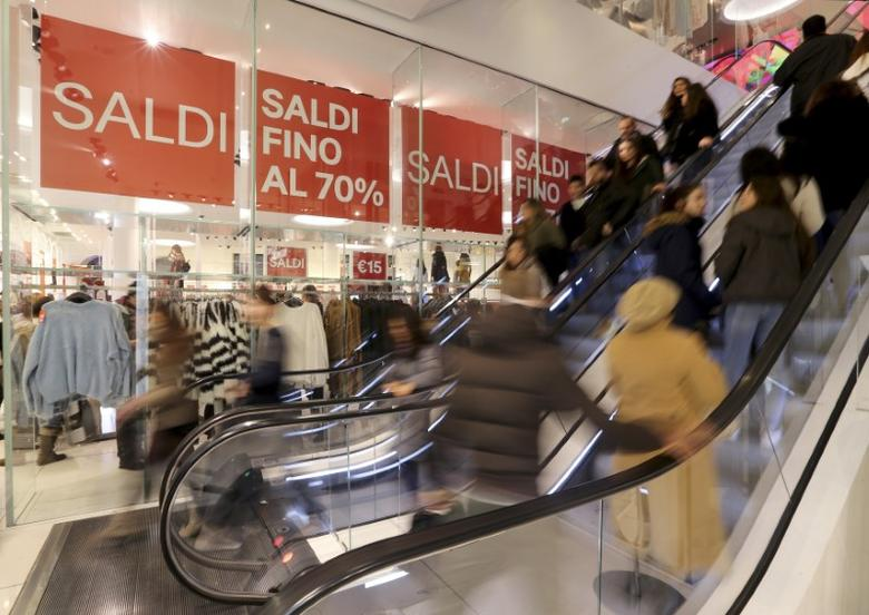 Signs that read, ''Up to 70% sales'' are seen on the first day of winter sales, as people enter a shop in central Rome January 3, 2015. REUTERS/Alessandro Bianchi
