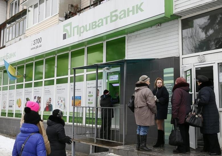 People gather near an automated teller machine (ATM) outside a PrivatBank branch in Kiev, Ukraine, December 19, 2016. REUTERS/Valentyn Ogirenko