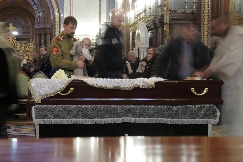 People walk past the coffin containing the body of Russian ambassador to Turkey Andrei Karlov, who was shot dead by an off-duty policeman while delivering a speech in an Ankara art gallery on December 19, during a memorial service at the Christ the Savior Cathedral in Moscow, Russia December 22, 2016. REUTERS/Maxim Shemetov