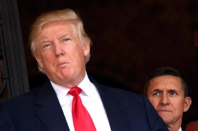 U.S. Army Lieutenant General Michael Flynn looks at U.S. President-elect Donald Trump as he talks with the media at Mar-a-Lago estate where Trump attends meetings, in Palm Beach, Florida, U.S., December 21, 2016. REUTERS/Carlos Barria